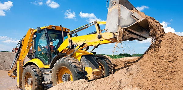 Excavator machine unloading sand at construction site