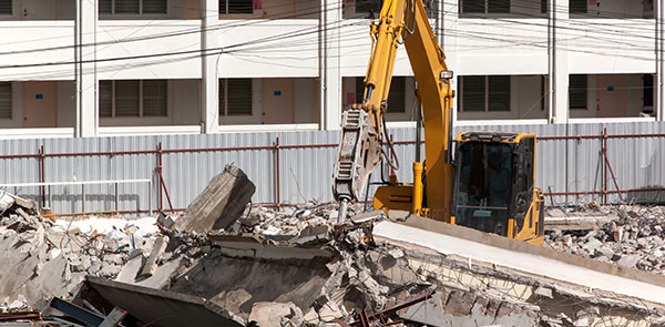 Jack hammer excavator demolishing old building