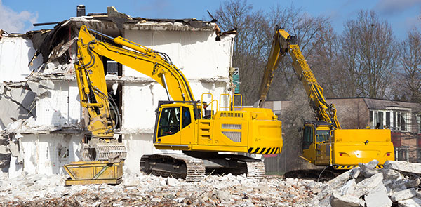 Two yellow demolition cranes dismantling building